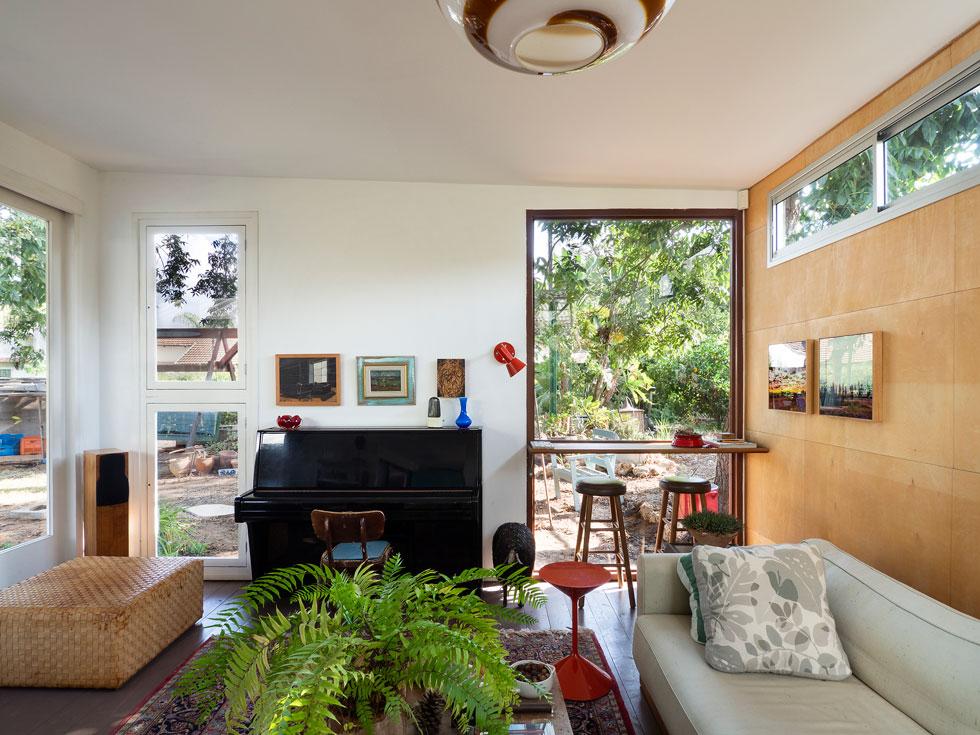כל אחד מהפתחים שונה, הקיר צופה בלוחות דקיקים של עץ ליבנה, והרהיטים נקנו לפני שנים בחנויות איכותיות (צילום: נגה שחם פורת)