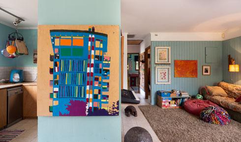 על מחיצת העץ שמפרידה בין המטבח לסלון ציור של ברק בנדל, מיריד ''צבע טרי'' בתחילת דרכו (צילום: נגה שחם פורת)
