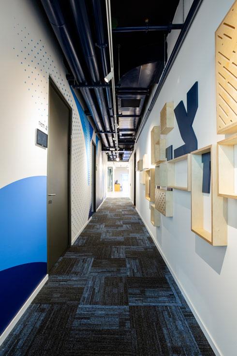 אחת הקומות של החברה. הצבע השולט הוא כחול - בשטיח, בקירות וגם בצינורות התשתית שצמודים לתקרה (צילום: דור נבו)