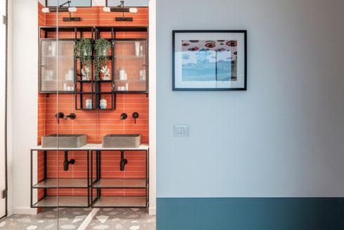 מבט מהכניסה. פינת הרחצה שמחוץ לשירותי האורחים מוכפלת במראה, וההדפס על הקיר הוא עיבוד גרפי של צילום מאלבומים משפחתיים (צילום: אביעד בר נס)