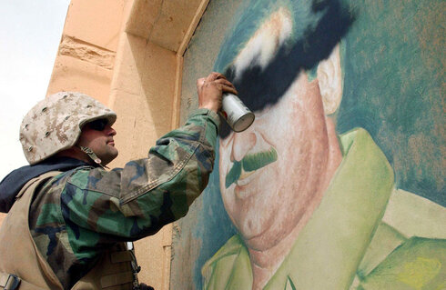 U.S. soldier spray paints over image of Saddam Hussein in 2003