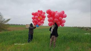 Hamas terrorists launching incendiary balloons into Israel