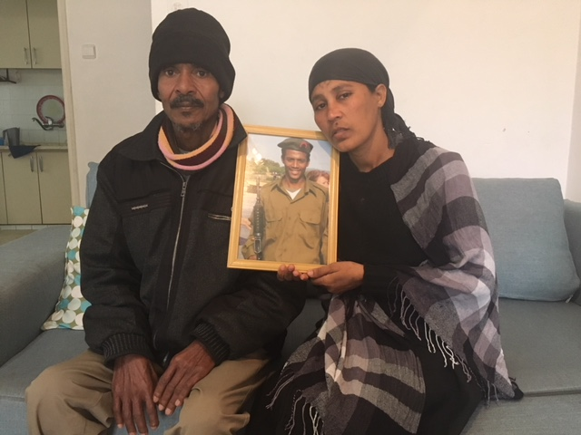 Atalay and Mamey Biadga sit in their Lod living room with a picture of their son, Yehuda, who was killed a year ago by police.
