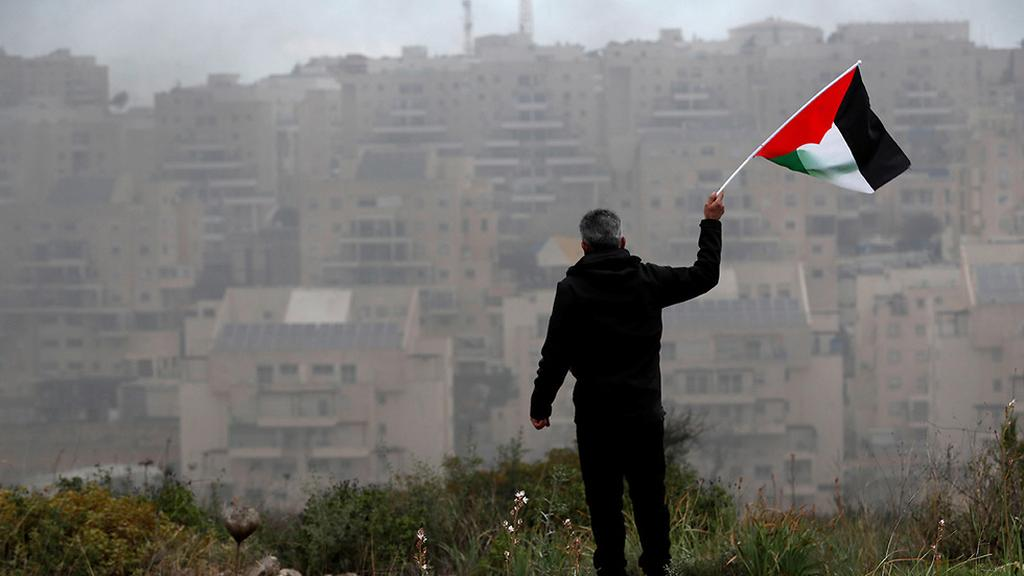 פלסטיני מנופף ב דגל פלסטין מול מודיעין עילית