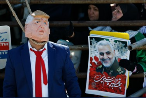 A man dressed as an effegy of U.S. President Trump next to a picture of Qassem Soleimani