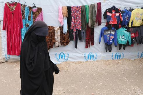 A woman walks past hung up clothes in al-Hol camp