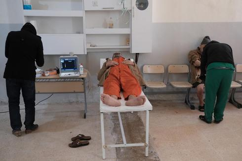 A foreign prisoner lies on top of an examining table next to a doctor inside a prison in Hasaka