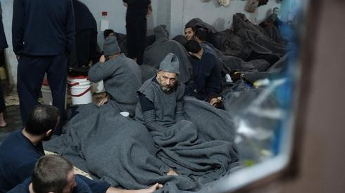 Prisoners lie inside a prison cell in Hasaka