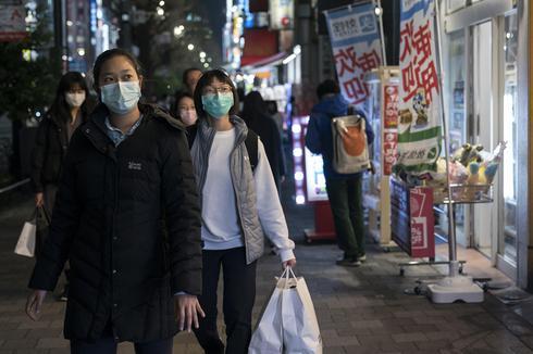 אנשים עם מסכות עושים קניות ב טוקיו יפן נגיף קורונה