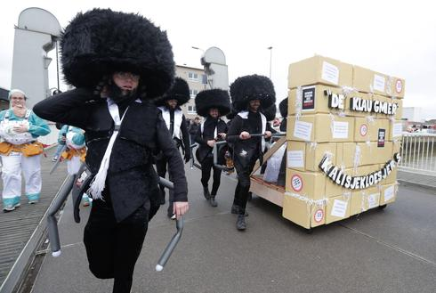 People dress as caricatures of Orthdox Jews with a mock Western Wall at the parade in Aalst, Feb. 23 2020