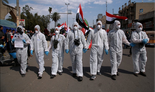 Anti-government protesters wear hazmat-like suits and gas masks during a rally in Baghdad