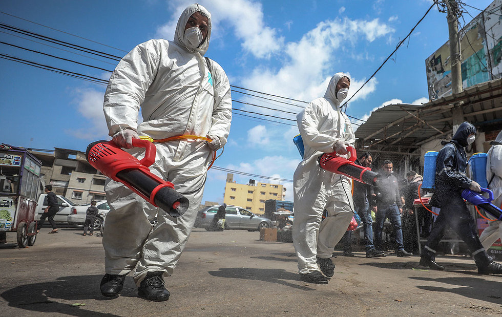 Health workers disinfect the streets in the Gaza Strip