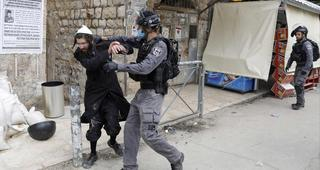 Israeli security forces arrest an Ultra Orthodox Jewish man as they close a synagogue in the Mea Shearim Ultra-Orthodox neighborhood in Jerusalem, amid efforts to curb the spread of the COVID-19 coronavirus pandemic