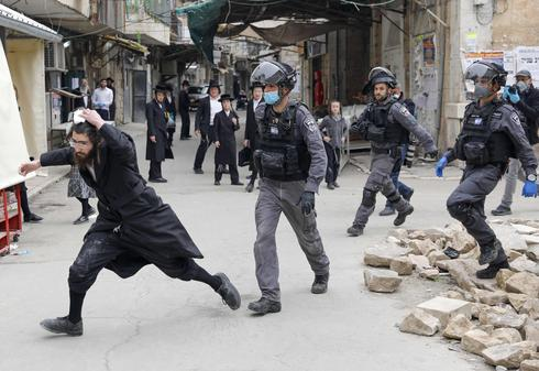 Israeli security forces arrest an Ultra Orthodox Jewish man as they close a synagogue in the Mea Shearim Ultra-Orthodox neighbourhood in Jerusalem, amid efforts to curb the spread of the COVID-19 coronavirus pandemic.