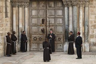 Franciscan monks pray in front of the closed door of the Church of the Holy Sepulchre