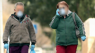 An Israeli woman wearing mask and gloves against coronavirus infection uses her cell phone