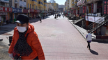 A resident wearing a face mask walks past a shopping street in Suifenhe, China