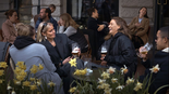People chat and drink outside a bar in Stockholm, Sweden