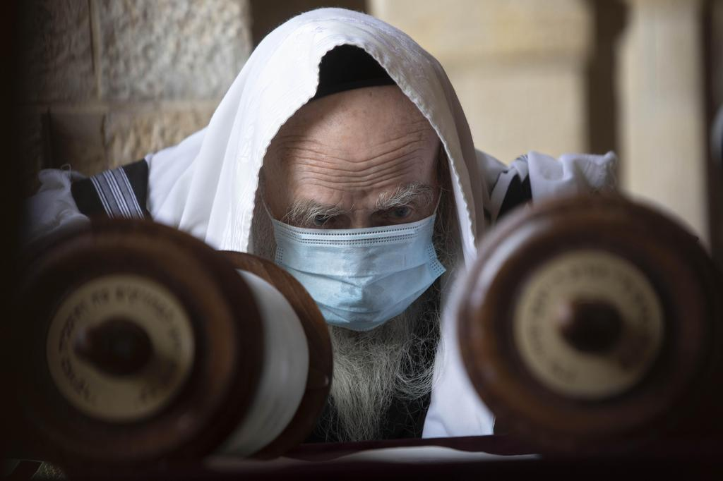 A man wears a face mask to curb the spread of the coronavirus as he reads from a Torah scroll at the Western Wall, the holiest site where Jews can pray in Jerusalem's old city