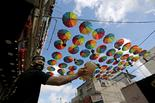 A Palestinian worker in the southern Gaza Strip sprays water outside shops decorated for Ramadan, amid concerns about the spread of coronavirus