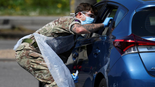 A member of the military tests a person at a coronavirus test centre in the car park of Chessington World of Adventures, Chessington, Britain