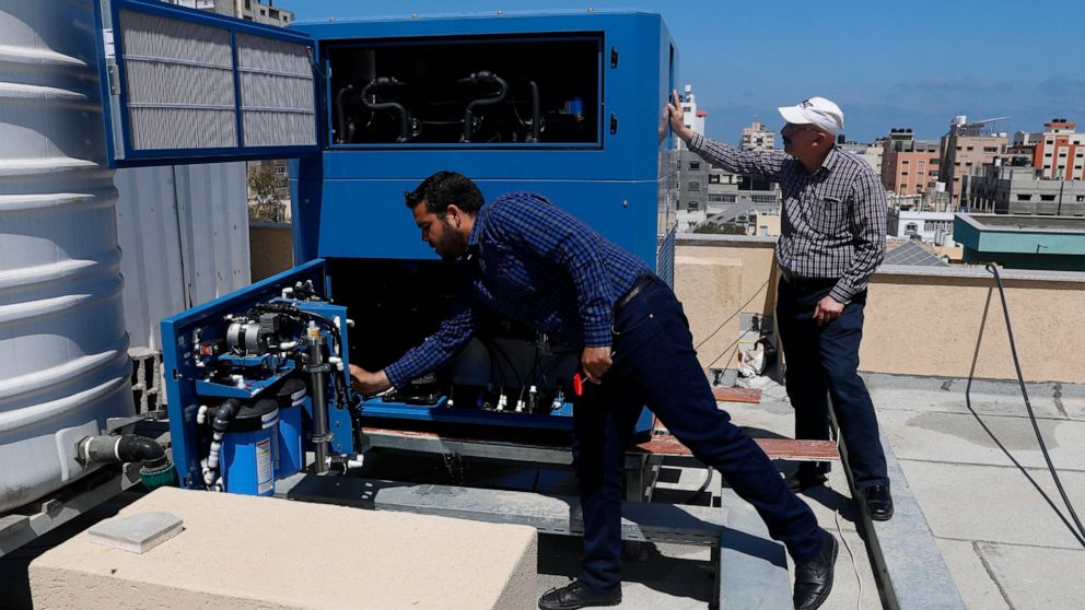 Palestinian engineer Raed Nakhal from Palestine Children Relief Fund, right, and engineer Abdullah Dewik, check the GEN-M machine that generates safe drinking water from air at the roof of al-Rantisi pediatric hospital in Gaza City