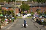 resident carries shopping bags as houses are decorated in bunting to mark the 75th anniversary of VE Day