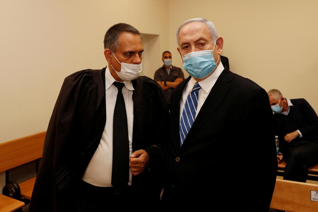 Prime Minister Benjamin Netanyahu stands inside the courtroom as his corruption trial opens at the Jerusalem District Court, May 24, 2020