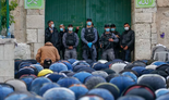 Israeli security forces clad in masks due to the coronavirus pandemic look on as Muslim worshipers gather to attend the prayers of Eid al-Fitr outside the closed Aqsa mosque complex in Jerusalem's old city