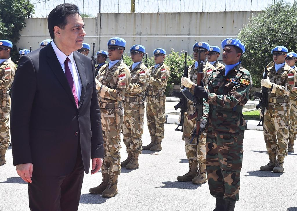 Lebanese Prime Minister Hassan Diab reviews the honor guard of the United Nations peacekeepers, upon his arrival at their headquarters in the southern coastal border town of Naqoura