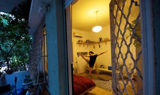 Yael Ben Ezer, a dancer from Israel's Batsheva Dance Company, is seen through a window while she practices in her apartment