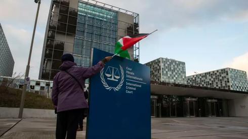 Un manifestante posa con una bandera palestina fuera de la Corte Penal Internacional