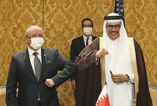 Israel's national security adviser, Meir Ben-Shabbat, left, bumps elbows with Bahrain's Foreign Minister Abdullatif al-Zayani after signing an agreement in Manama, Bahrain