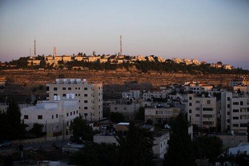 Part of the Israeli settlement of Psagot, top, overlooks Palestinian the West Bank city of Al-Bireh