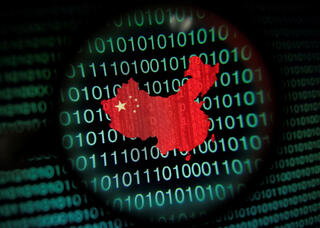 A map of China is seen through a magnifying glass on a computer screen showing binary digit, illustration