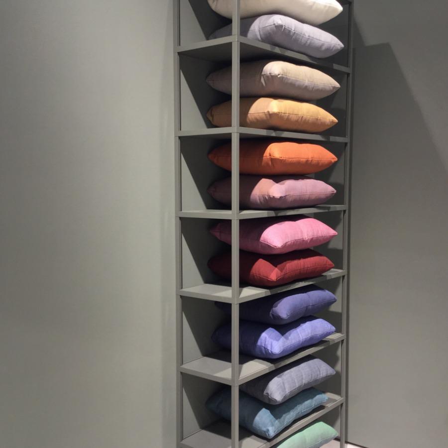 כריות של חברת HAY בשלל גוונים מעושנים, על מדפים בגוון הקיר - אפור ירקרק. גם המונוכרום שולט.