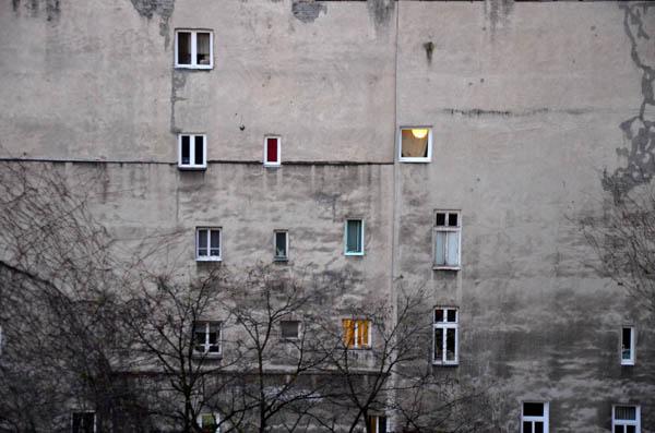 קיר אש אטום של בלוק עירוני לחזית מחוררת ויפיפיה כאשר דייריו פרצו בו חלונות זה אחר זה, ללא תכנון וללא סדר מוכתב.   ( Talmon Biran Architecture Studio)