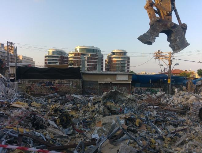 כלי כבד בשטח ההריסה וברקע צמרות מגדלי רביעיית פלורנטין הסמוכים. סמטת המחוגה, 17 ביולי 2016