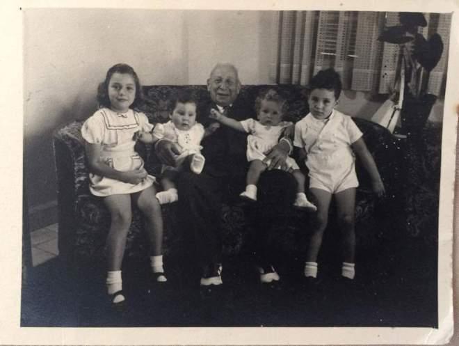סבא משה עם הנכדים בבית המשפחה, 1949. בגב הצילום כתב: