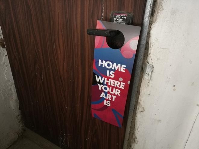 כמה ציני אפשר להיות? פלייר של פרויקט וילג' על דלת בבניין ישן ברחוב בן עטר, 11 בינואר 2017