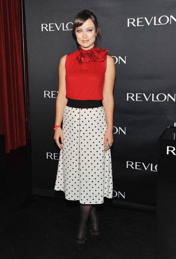 אוליבייה וויילד אלגנטית בחולצה אדומה וחצאית לבנה עם נקודות (צילום: gettyimages)