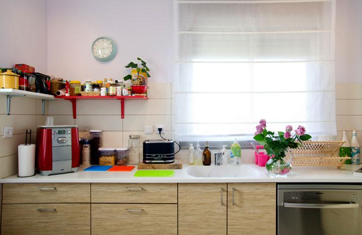 למטבח הקבלני המצוי נוספו מעט פריטים: שעון, שני מדפים צבעוניים ולוח מודעות מזכוכית אדומה (צילום: אילן נחום)