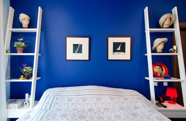 הקיר בגב המיטה נצבע בכחול עמוק. שני סולמות מדפים הוזמנו אצל נגר בפחות מחצי ממחירם בחנות יוקרה. מעל המיטה מוסגרו צילומים מתוך ספר של רוברט מייפלת'ורפ (צילום: אילן נחום)
