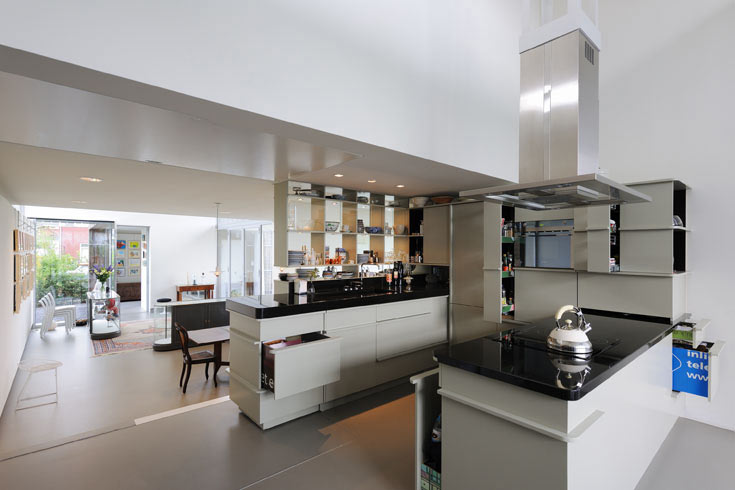 ארונות המטבח, הצבועים לבן מבריק, מורכבים משלטי חוצות ישנים. כאשר פותחים את הדלתות והמגירות מתגלה עברן הצבעוני (צילום: Allard van der Hoek - Architektuurfotografie )