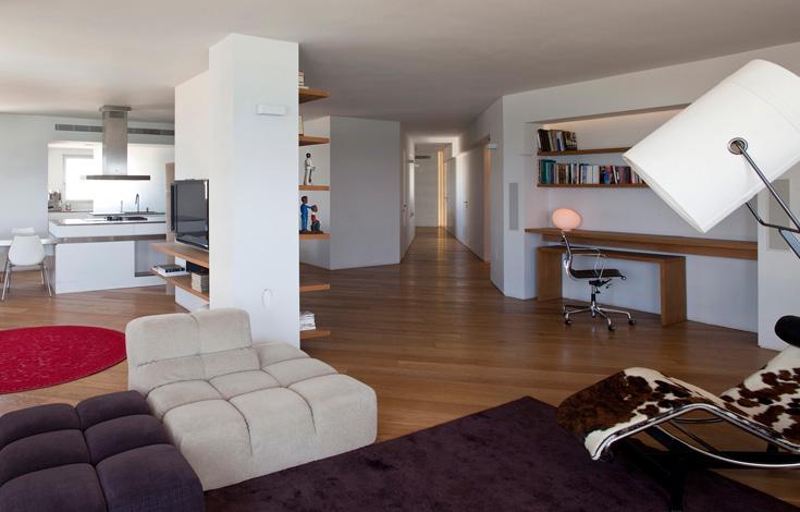 שתי דירות אוחדו לאחת, בעלת קווים ארוכים ונקיים. המסדרון הגיאומטרי הוא אזור החיבור בין הדירות המקוריות: האחת הפכה לאזור חדרי השינה והעבודה, השנייה לאגף המשפחתי המשותף, שכולל סלון, מטבח ופינות אוכל, טלוויזיה ומוסיקה. בסלון הוצבה ספת פוף מודולרית נטולת רגליים, שמאפשרת משחק ושינוי בהתאם לצורך ולרצון בני הבית (BItaly&B) (צילום: עמית גרון)