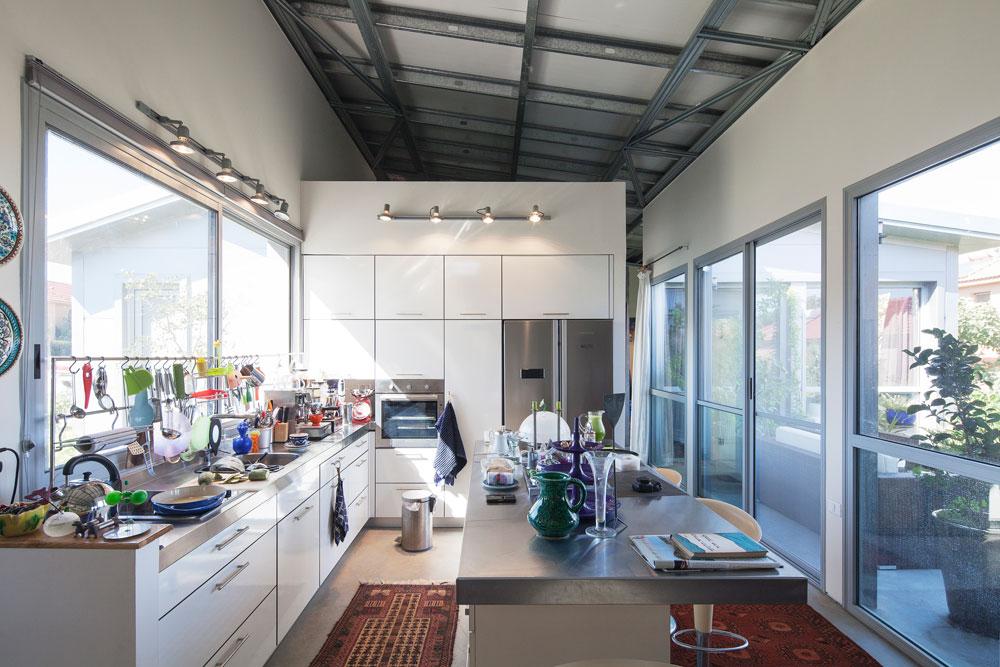 ארונות המטבח מחופים פורמייקה לבנה, משטח העבודה ומתקן התלייה לכלי הבישול עשויים נירוסטה. רצפת הבטון של הבית נותרה חשופה, וכך גם התקרה. הבחירה הוזילה מאוד את עלות הבית - 460 אלף שקלים בסך הכל, כולל הכל (צילום: אביעד בר נס)