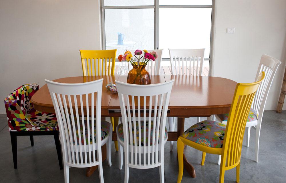 פינת האוכל היא הרהיט היחיד שהובא מהבית הקודם. בשולחן לא נגעו, אך הכסאות נצבעו בצהוב ולבן ומושביהם רופדו מחדש. כדי לשבור את ה''סט'' הוצבה בראש השולחן כורסה צבעונית (צילום: יוראי לברמן)