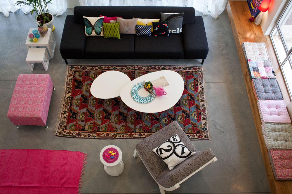 הספה הכהה היא הרהיט היקר ביותר בבית. את רצינותה מאזנות כריות עם הדפסים צבעוניים, כפי שאת רצפת הבטון ''מחמם'' שטיח מעוטר שנקנה בשוק הפשפשים. כריות צבעוניות הונחו גם על ספסל עץ מאסיבי, שנתלה לאורך הקיר מתחת לחלון (צילום: יוראי לברמן)