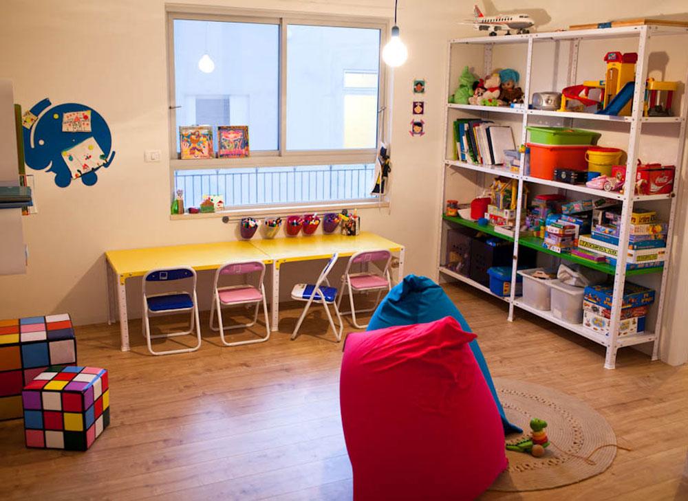 חדר המשחקים של הילדים רוהט במדפים ושולחן יצירה תעשייתיים ממתכת, שנצבעו בצבעים עליזים. הדומים בצורת קובייה הונגרית נקנו במכירת החיסול של  ''קיקה'' (צילום: יוראי לברמן)