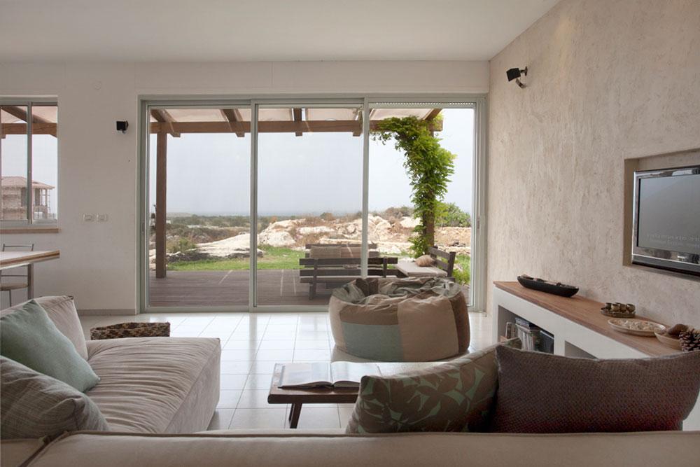 הסלון פונה לים, ונבחרו לו גוונים תכולים וחוליים, שמשתלבים עם החוץ ומזכירים לבעלי הבית אדריכלים ''מקסיקנים מודרניים, כמו לואיס ברגאן'' (צילום: גידי בועז)